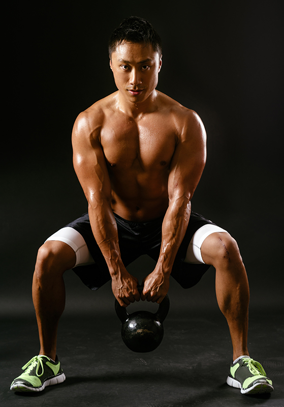 man does squat with kettlebell