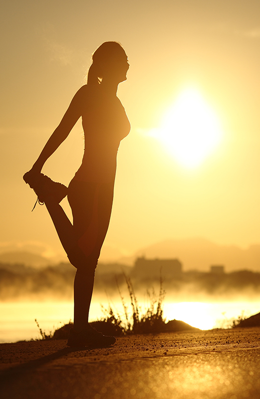 Silhouette of a woman stretching at sunrise with the sun in the background