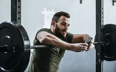 Man reviews video on his phone while resting on squat bar.