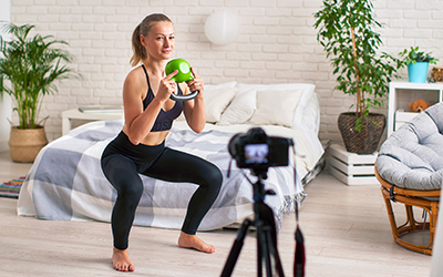Woman records herself doing a kettlebell squat.