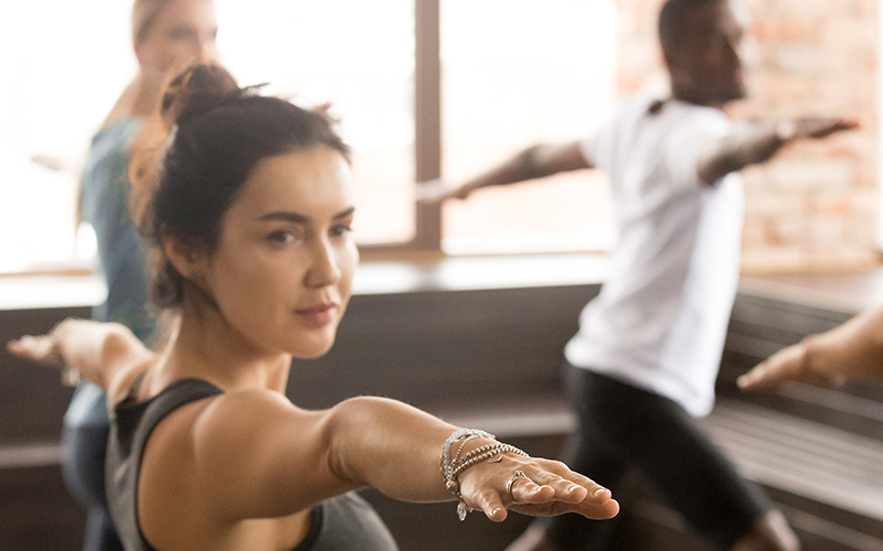 Woman doing Yoga at the front of the class.