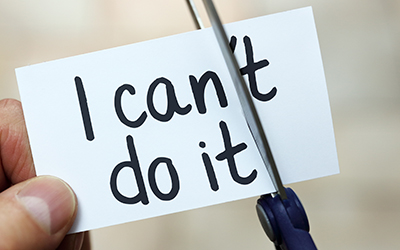 """Person uses a pair of scissors to turn """"I can't do it"""" written on a card into """"I can do it"""""""