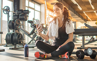 Woman watches video of workout on her phone during a rest period.