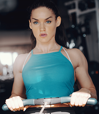 A woman visualizes her success on the rowing machine.