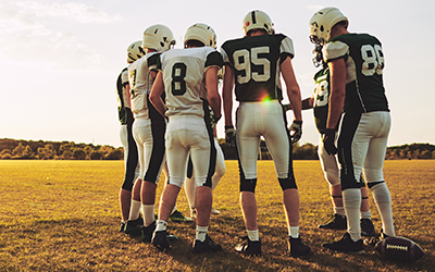 Football players discuss their plan before executing a play.