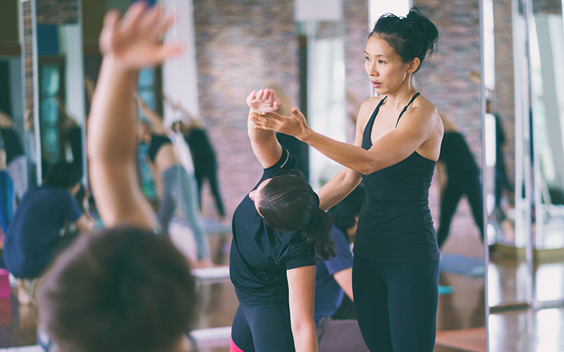 Yoga instructor helps a student with their pose.