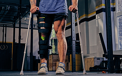 Athlete with brace on one leg and crutches engages in physical therapy.