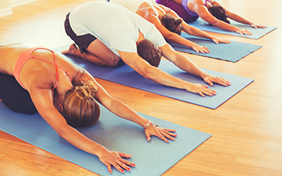 group of athletes perform yoga as a recovery exercise.