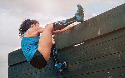 Woman climbs wall during obstacle race.