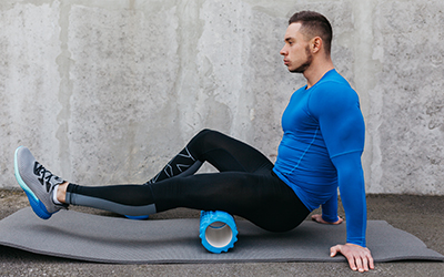 Man uses foam roller for recovery post workout.