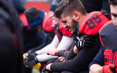 Football player sits on sideline holding arm