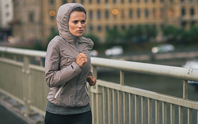 Woman runs across bridge in cold and rainy weather.