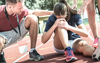 Runner deals with an injury on the track with coach and trainer by her side.