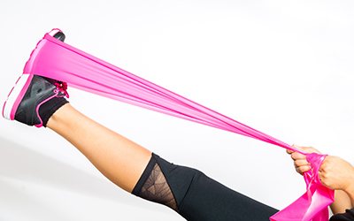 Athlete uses a resistance band to increase the intensity of a stretch.