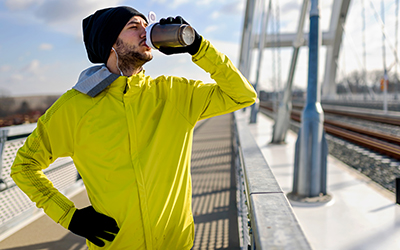man in yellow coat stops in his outdoor training to take a drink of water.