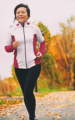 Woman runs dressed in appropriate cold weather training gear.
