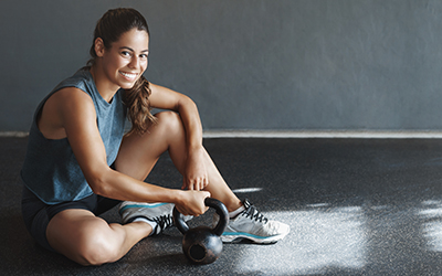 Female athlete sits on the floor, smiling, holding a kettlebell.