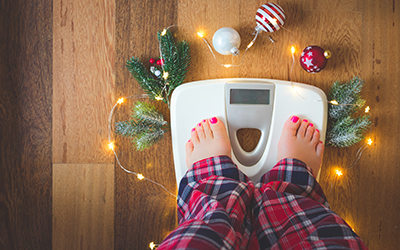 Person checks weight on the scale at the end of the holiday season.