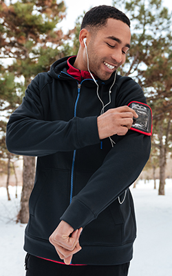 Man adjusts his music player before getting started with cold weather training.