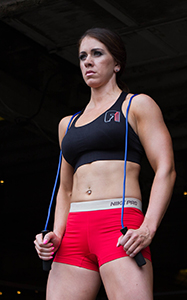 Woman with toned abs stands with jump rope over her shoulders.