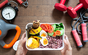 Person holds a pre-workout meal in a white bowl surrounded by exercise accessories.