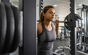 Female athlete prepares for a high intensity, low rep session at the squat rack.