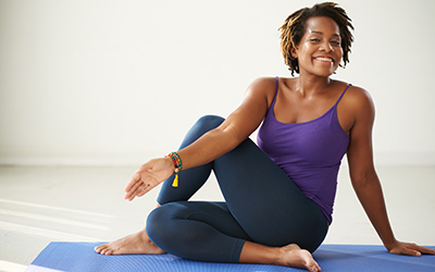 Woman in purple tank top performs a seated trunk twist.