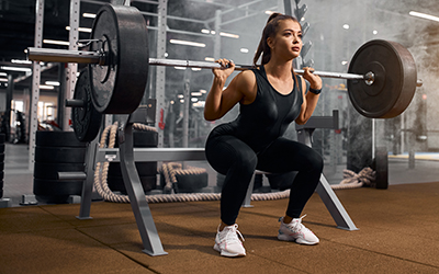 Female athlete performs a weighted squat with a bar bell.
