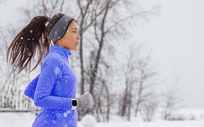 Woman runs as it snows.
